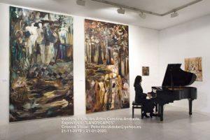 Sala de exposiciones museo con cuadros gigantes y chica tocando el piano