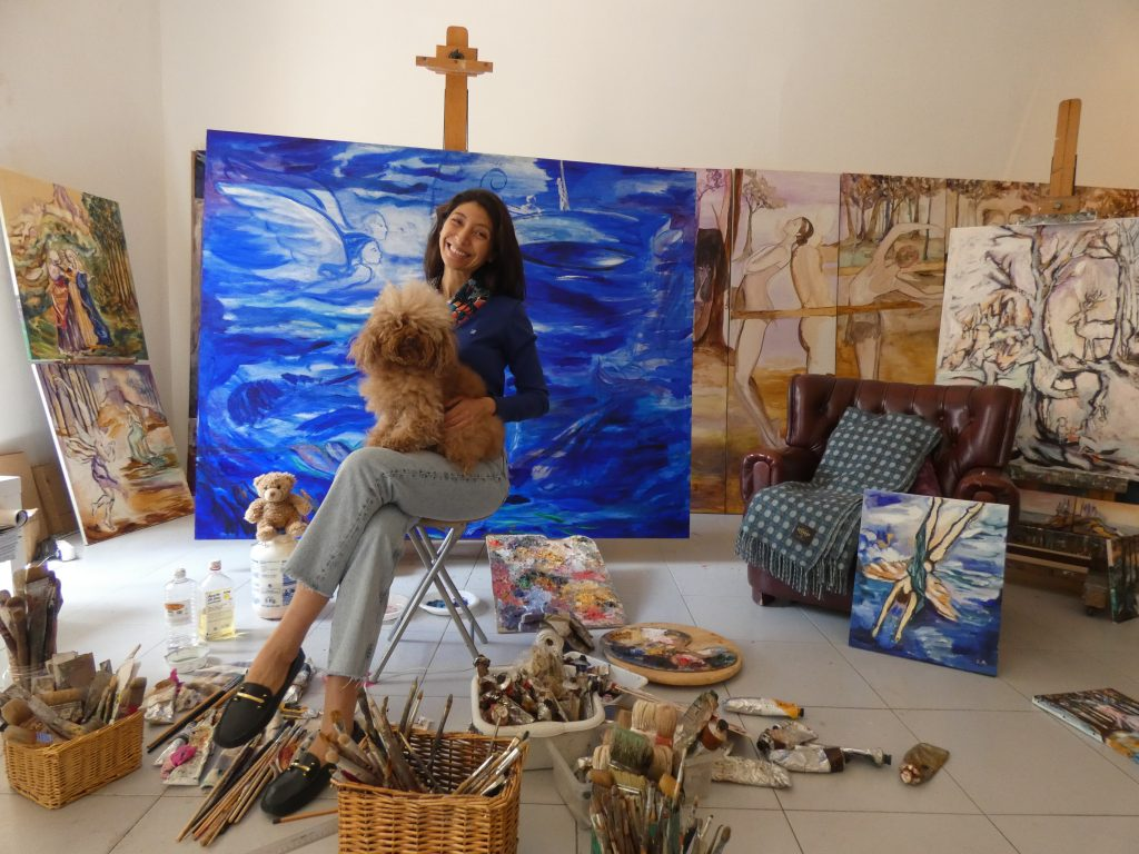 carolina andrada pintora en estudio con cuadros y perro caniche marrón